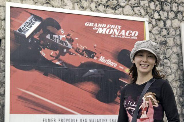 モンテカルロ市内で大好きなフェラーリの看板の前で我が女王陛下。