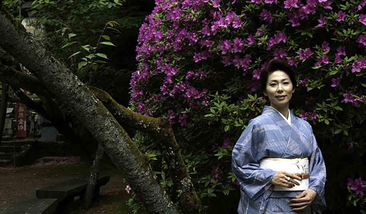 長岳寺のツツジを背景に着物姿の女王